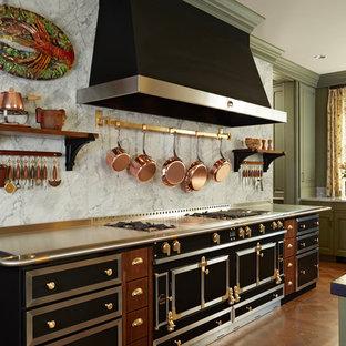 ミネアポリスの地中海スタイルのおしゃれなダイニングキッチン (レイズドパネル扉のキャビネット、ヴィンテージ仕上げキャビネット、白いキッチンパネル、石スラブのキッチンパネル、黒い調理設備、アンダーカウンターシンク、ステンレスカウンター、無垢フローリング、オレンジの床) の写真