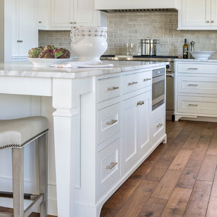 Eat-in kitchen - mid-sized traditional l-shaped dark wood floor eat-in kitchen idea in Minneapolis with an undermount sink, recessed-panel cabinets, white cabinets, marble countertops, gray backsplash, ceramic backsplash, an island and stainless steel appliances