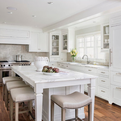 Kitchen - mid-sized traditional l-shaped dark wood floor kitchen idea in Minneapolis with recessed-panel cabinets, subway tile backsplash, paneled appliances, white cabinets, marble countertops, gray backsplash, an undermount sink, an island and white countertops