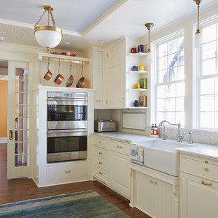 Klassische Wohnküche ohne Insel in U-Form mit Landhausspüle, profilierten Schrankfronten, weißen Schränken, Quarzit-Arbeitsplatte, Küchenrückwand in Weiß, Rückwand aus Porzellanfliesen, Küchengeräten aus Edelstahl und dunklem Holzboden in Minneapolis