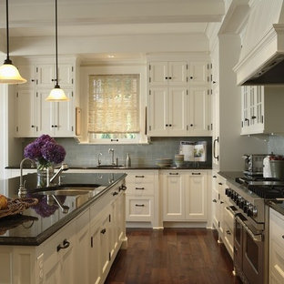 Traditional eat-in kitchen designs - Example of a classic l-shaped medium tone wood floor eat-in kitchen design in Minneapolis with an undermount sink, shaker cabinets, white cabinets, blue backsplash, subway tile backsplash, stainless steel appliances and an island