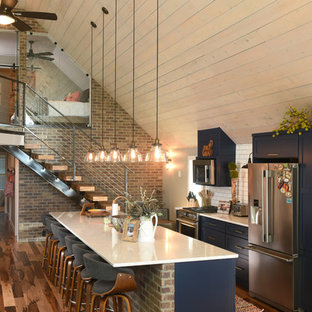 Kitchen - rustic galley medium tone wood floor and brown floor kitchen idea in Other with shaker cabinets, blue cabinets, white backsplash, subway tile backsplash, stainless steel appliances, an island and white countertops
