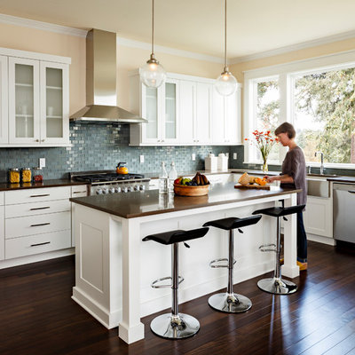 Example of a mid-sized transitional galley dark wood floor kitchen design in Portland with a farmhouse sink, shaker cabinets, white cabinets, mosaic tile backsplash, stainless steel appliances, an island, brown countertops, quartz countertops and brown backsplash