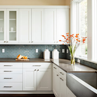 This is an example of a mid-sized transitional galley separate kitchen in Portland with a farmhouse sink, blue splashback, white cabinets, shaker cabinets, quartz benchtops, with island, brown benchtop, mosaic tile splashback, stainless steel appliances and dark hardwood floors.