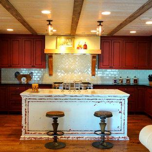 Offene, Mittelgroße Landhausstil Küche in U-Form mit Landhausspüle, Kassettenfronten, roten Schränken, Marmor-Arbeitsplatte, Küchenrückwand in Weiß, Rückwand aus Keramikfliesen, Küchengeräten aus Edelstahl, braunem Holzboden und Kücheninsel in Boise