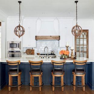 Idee per una cucina costiera con ante in stile shaker, ante bianche, paraspruzzi bianco, elettrodomestici in acciaio inossidabile, parquet scuro, un'isola e top bianco