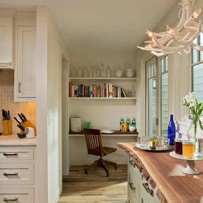 Small transitional l-shaped medium tone wood floor eat-in kitchen photo in Boston with a farmhouse sink, recessed-panel cabinets, dark wood cabinets, marble countertops, beige backsplash, matchstick tile backsplash and stainless steel appliances