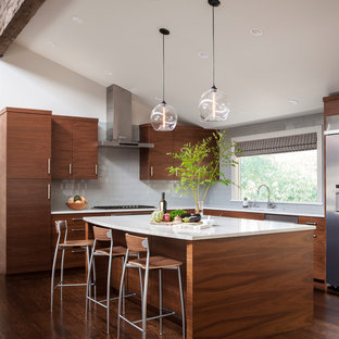Idéer för att renovera ett mycket stort 60 tals kök, med en undermonterad diskho, släta luckor, skåp i mörkt trä, marmorbänkskiva, grått stänkskydd, stänkskydd i glaskakel, rostfria vitvaror, mörkt trägolv och en köksö