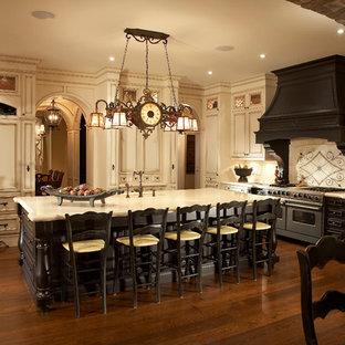 Неиссякаемый источник вдохновения для домашнего уюта: большая п-образная кухня в классическом стиле с бежевыми фасадами, бежевым фартуком, техникой под мебельный фасад, обеденным столом, фасадами с утопленной филенкой, столешницей из гранита, островом, темным паркетным полом, фартуком из известняка и бежевой столешницей