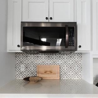 シアトルの大きいインダストリアルスタイルのおしゃれなキッチン (エプロンフロントシンク、シェーカースタイル扉のキャビネット、白いキャビネット、クオーツストーンカウンター、マルチカラーのキッチンパネル、セメントタイルのキッチンパネル、シルバーの調理設備の、濃色無垢フローリング、茶色い床、マルチカラーのキッチンカウンター) の写真