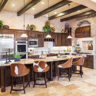 This is an example of a large mediterranean l-shaped open plan kitchen in Houston with a farmhouse sink, raised-panel cabinets, dark wood cabinets, beige splashback, stainless steel appliances, with island, beige floor, granite benchtops, travertine floors and beige benchtop.