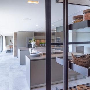 チェシャーの大きいコンテンポラリースタイルのおしゃれなキッチン (一体型シンク、フラットパネル扉のキャビネット、中間色木目調キャビネット、ステンレスカウンター、木材のキッチンパネル、シルバーの調理設備の、セラミックタイルの床、白い床、緑のキッチンカウンター) の写真