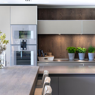 Photo of a large contemporary open plan kitchen in Cheshire with an integrated sink, flat-panel cabinets, medium wood cabinets, stainless steel benchtops, timber splashback, stainless steel appliances, ceramic floors, multiple islands, white floor and green benchtop.