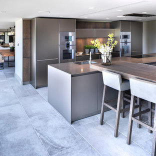 This is an example of a large contemporary open plan kitchen in Cheshire with an integrated sink, flat-panel cabinets, medium wood cabinets, stainless steel benchtops, timber splashback, stainless steel appliances, ceramic floors, multiple islands, white floor and green benchtop.