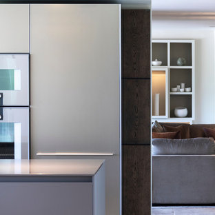 Design ideas for a large contemporary open plan kitchen in Cheshire with an integrated sink, flat-panel cabinets, medium wood cabinets, stainless steel benchtops, timber splashback, stainless steel appliances, ceramic floors, multiple islands, white floor and green benchtop.