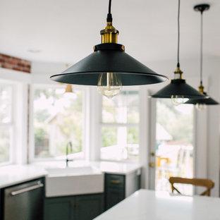 シアトルの小さいインダストリアルスタイルのおしゃれなキッチン (エプロンフロントシンク、シェーカースタイル扉のキャビネット、グレーのキャビネット、珪岩カウンター、赤いキッチンパネル、レンガのキッチンパネル、シルバーの調理設備の、濃色無垢フローリング、茶色い床、白いキッチンカウンター) の写真