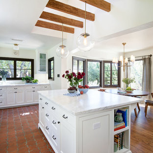 Large mediterranean l-shaped eat-in kitchen in Los Angeles with beaded inset cabinets, white cabinets, marble benchtops, white splashback, terra-cotta floors, with island and orange floor.