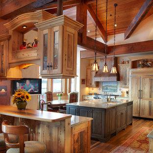 デンバーの大きいラスティックスタイルのおしゃれなキッチン (アンダーカウンターシンク、レイズドパネル扉のキャビネット、淡色木目調キャビネット、御影石カウンター、マルチカラーのキッチンパネル、トラバーチンの床、パネルと同色の調理設備、無垢フローリング、緑のキッチンカウンター) の写真