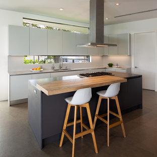 Moderne Küche in L-Form mit Doppelwaschbecken, flächenbündigen Schrankfronten, weißen Schränken, Küchenrückwand in Weiß, Rückwand-Fenster, Betonboden, Kücheninsel, grauem Boden und grauer Arbeitsplatte in Miami