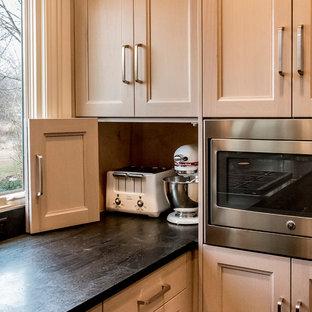 Photo of a medium sized traditional l-shaped kitchen pantry in Chicago with a submerged sink, flat-panel cabinets, grey cabinets, quartz worktops, black splashback, stone slab splashback, medium hardwood flooring and an island.