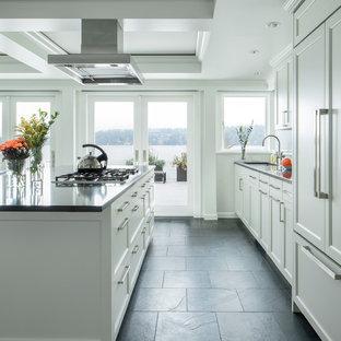 Immagine di una cucina tradizionale con lavello sottopiano, ante con riquadro incassato, ante bianche, top in quarzo composito, paraspruzzi bianco, elettrodomestici da incasso, pavimento in ardesia, pavimento nero e top grigio