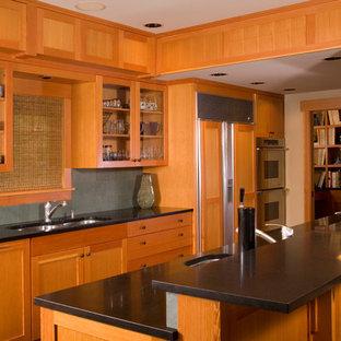 Ejemplo de cocina de galera, de estilo americano, con fregadero bajoencimera, armarios estilo shaker, puertas de armario de madera oscura, encimera de granito, electrodomésticos con paneles, salpicadero verde y salpicadero de piedra caliza