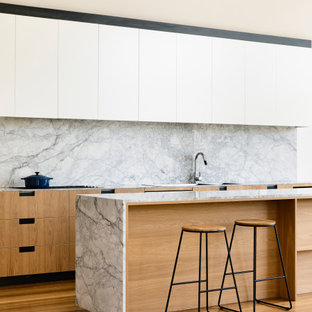 Inspiration for a contemporary galley kitchen in Geelong with flat-panel cabinets, white cabinets, grey splashback, stone slab splashback, medium hardwood floors, with island, brown floor and grey benchtop.