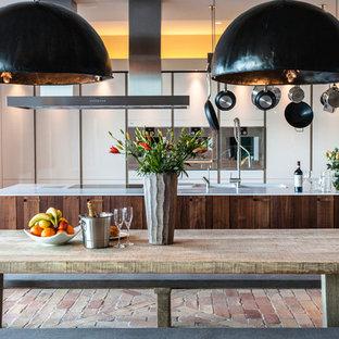 Foto de cocina de galera, rústica, abierta, con fregadero integrado, armarios con paneles lisos, puertas de armario blancas, electrodomésticos con paneles, suelo de ladrillo y una isla