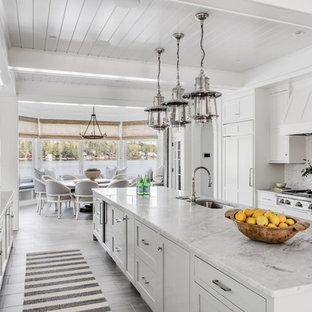 Idéer för att renovera ett maritimt kök och matrum, med en undermonterad diskho, skåp i shakerstil, vita skåp, marmorbänkskiva, vitt stänkskydd, stänkskydd i marmor, integrerade vitvaror och en köksö