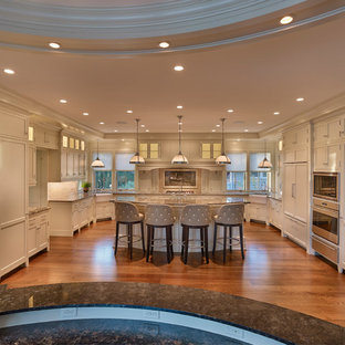 Photo of an expansive traditional u-shaped eat-in kitchen in Other with a farmhouse sink, recessed-panel cabinets, white cabinets, limestone benchtops, beige splashback, travertine splashback, panelled appliances, dark hardwood floors, with island, brown floor and brown benchtop.