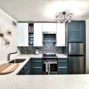 Small midcentury u-shaped eat-in kitchen in Chicago with a single-bowl sink, flat-panel cabinets, turquoise cabinets, quartz benchtops, multi-coloured splashback, glass tile splashback, stainless steel appliances, dark hardwood floors, a peninsula, brown floor and white benchtop.