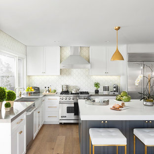 Example of a mid-sized transitional l-shaped light wood floor and beige floor eat-in kitchen design in Los Angeles with white cabinets, stainless steel appliances, an island, a farmhouse sink, recessed-panel cabinets and beige backsplash