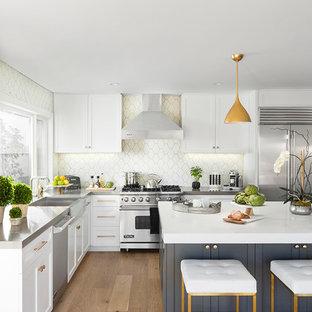 Esempio di una cucina chic di medie dimensioni con ante bianche, elettrodomestici in acciaio inossidabile, isola, lavello stile country, ante con riquadro incassato, paraspruzzi beige, parquet chiaro e pavimento beige