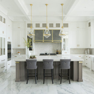 This is an example of an expansive transitional u-shaped eat-in kitchen in Chicago with a farmhouse sink, recessed-panel cabinets, white cabinets, quartzite benchtops, white splashback, stone slab splashback, panelled appliances, marble floors, with island, white floor and white benchtop.