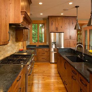 ワシントンD.C.の大きいラスティックスタイルのおしゃれなキッチン (アンダーカウンターシンク、シェーカースタイル扉のキャビネット、中間色木目調キャビネット、ベージュキッチンパネル、シルバーの調理設備の、無垢フローリング、ソープストーンカウンター、サブウェイタイルのキッチンパネル、茶色い床) の写真