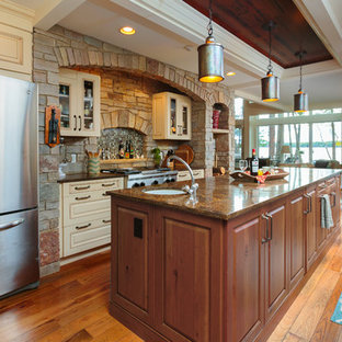 Large craftsman eat-in kitchen ideas - Example of a large arts and crafts medium tone wood floor eat-in kitchen design in Detroit with white cabinets, granite countertops, stainless steel appliances and an island