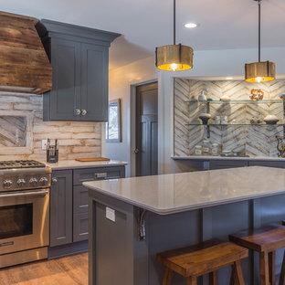 デトロイトの中サイズのシャビーシック調のおしゃれなキッチン (アンダーカウンターシンク、シェーカースタイル扉のキャビネット、グレーのキャビネット、クオーツストーンカウンター、白いキッチンパネル、磁器タイルのキッチンパネル、シルバーの調理設備の、クッションフロア、茶色い床) の写真