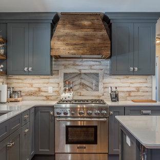 デトロイトの中サイズのシャビーシック調のおしゃれなキッチン (アンダーカウンターシンク、シェーカースタイル扉のキャビネット、グレーのキャビネット、クオーツストーンカウンター、白いキッチンパネル、磁器タイルのキッチンパネル、シルバーの調理設備、クッションフロア、茶色い床) の写真