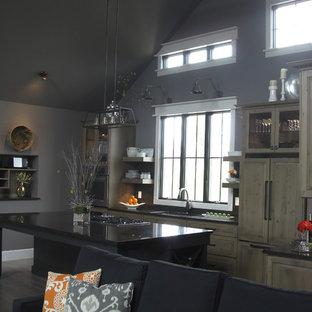 Mittelgroße Landhausstil Wohnküche in L-Form mit Unterbauwaschbecken, profilierten Schrankfronten, hellen Holzschränken, Granit-Arbeitsplatte, Küchenrückwand in Schwarz, Rückwand aus Glasfliesen, Elektrogeräten mit Frontblende, braunem Holzboden, Kücheninsel, beigem Boden und schwarzer Arbeitsplatte in Chicago