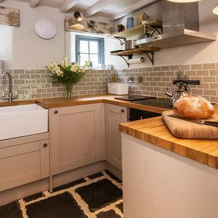 Идея дизайна: маленькая п-образная кухня-гостиная в стиле кантри с фасадами с утопленной филенкой, коричневыми фасадами, деревянной столешницей, серым фартуком, фартуком из керамической плитки, полом из бамбука и черным полом без острова