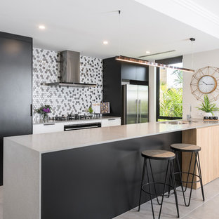 Photo of a mid-sized contemporary galley open plan kitchen in Perth with an undermount sink, flat-panel cabinets, black cabinets, concrete benchtops, black appliances, porcelain floors, grey floor, grey benchtop and multi-coloured splashback.