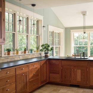 Exemple d'une cuisine craftsman avec un évier encastré, des portes de placards vertess, une crédence beige, un électroménager en acier inoxydable, une péninsule, un sol beige et un plan de travail noir.