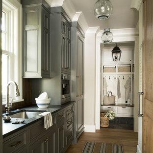 Ejemplo de cocina lineal, costera, con fregadero bajoencimera, armarios con paneles empotrados, puertas de armario grises, electrodomésticos con paneles, suelo de madera en tonos medios y suelo marrón