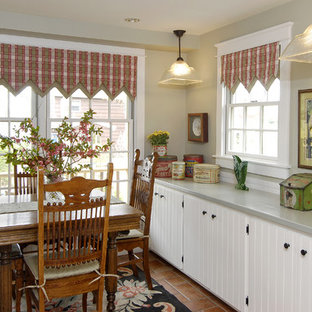 This is an example of a small country single-wall eat-in kitchen in Bridgeport with a drop-in sink, louvered cabinets, white cabinets and ceramic floors.