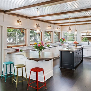 Transitional eat-in kitchen inspiration - Inspiration for a transitional u-shaped dark wood floor eat-in kitchen remodel in Milwaukee with a farmhouse sink, white cabinets, white backsplash, subway tile backsplash, an island, concrete countertops, stainless steel appliances and shaker cabinets