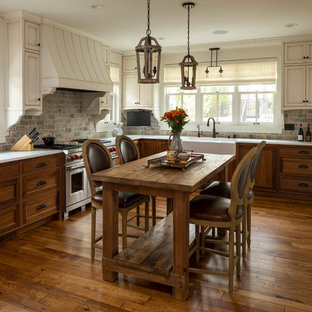 Mid-sized rustic eat-in kitchen pictures - Example of a mid-sized mountain style l-shaped dark wood floor and brown floor eat-in kitchen design in Minneapolis with a farmhouse sink, beaded inset cabinets, distressed cabinets, brown backsplash, brick backsplash, an island, white countertops and paneled appliances