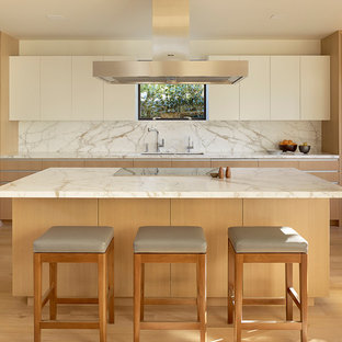This is an example of a midcentury eat-in kitchen in San Francisco with an undermount sink, flat-panel cabinets, light wood cabinets, marble benchtops, white splashback, stone slab splashback, panelled appliances, light hardwood floors and with island.