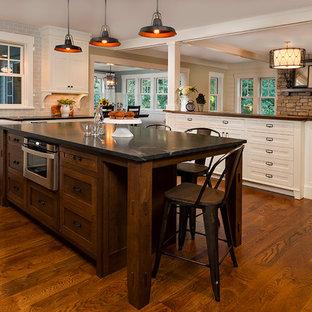 Foto på ett stort vintage kök, med en rustik diskho, skåp i shakerstil, vita skåp, bänkskiva i täljsten, blått stänkskydd, stänkskydd i tunnelbanekakel, rostfria vitvaror, mellanmörkt trägolv och en köksö