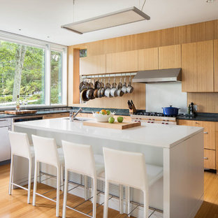 Contemporary kitchen ideas - Trendy l-shaped medium tone wood floor and brown floor kitchen photo in Boston with an undermount sink, flat-panel cabinets, medium tone wood cabinets, brown backsplash, stainless steel appliances, an island and black countertops