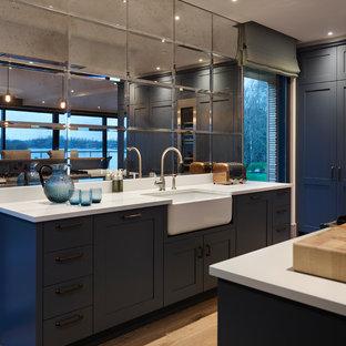 Contemporary kitchen in Gloucestershire with shaker cabinets, blue cabinets, metallic splashback, mirror splashback, light hardwood flooring, beige floors and white worktops.